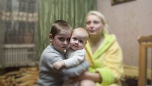Goncharova Iryna, beneficiary of a house rebuilt program me of the Luxembourg Red Cross, posses for the photo with her sons in Sloviansk, Donetsk area, Ukraine.